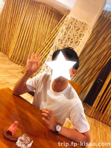 フランジパニ本館にあるカフェのテーブルの椅子に腰掛ける夫